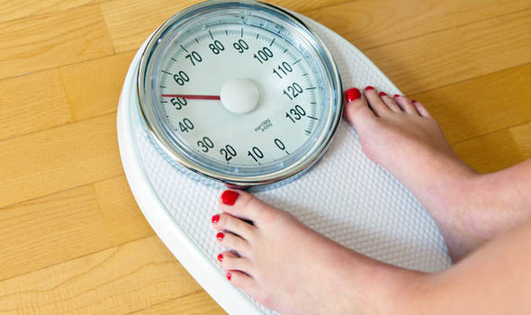 Woman-checking-her-weight-on-a-scale-585697